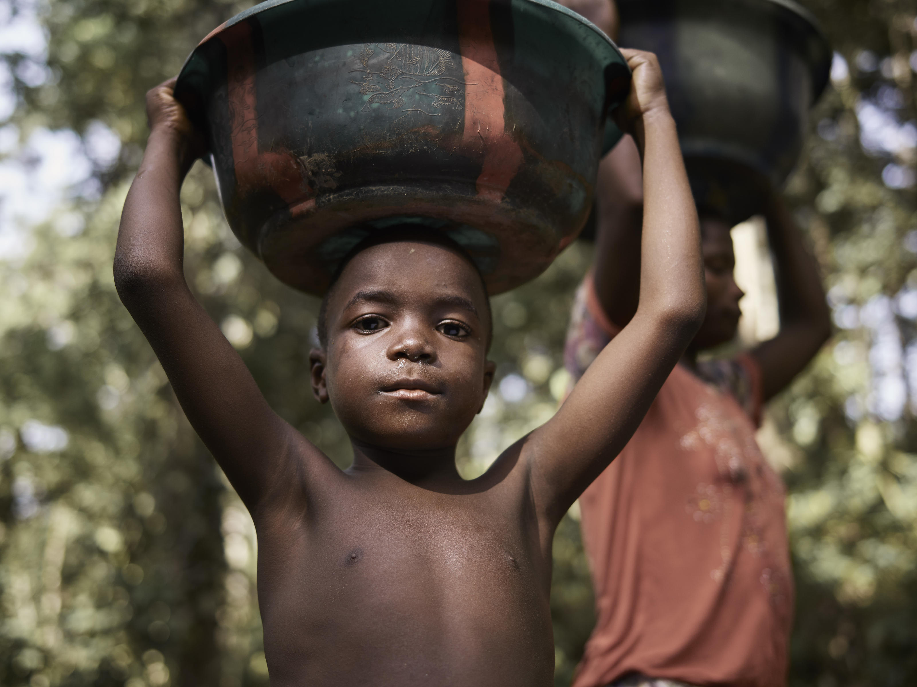 Lahai, 7, carries a basin of dirty water with his mother Matta Saffah, 27, as they make their way home from the previous dirty water source, a natural spring in the village of Tombohuaun. Everyone in the village has experienced persistent problems wit ...