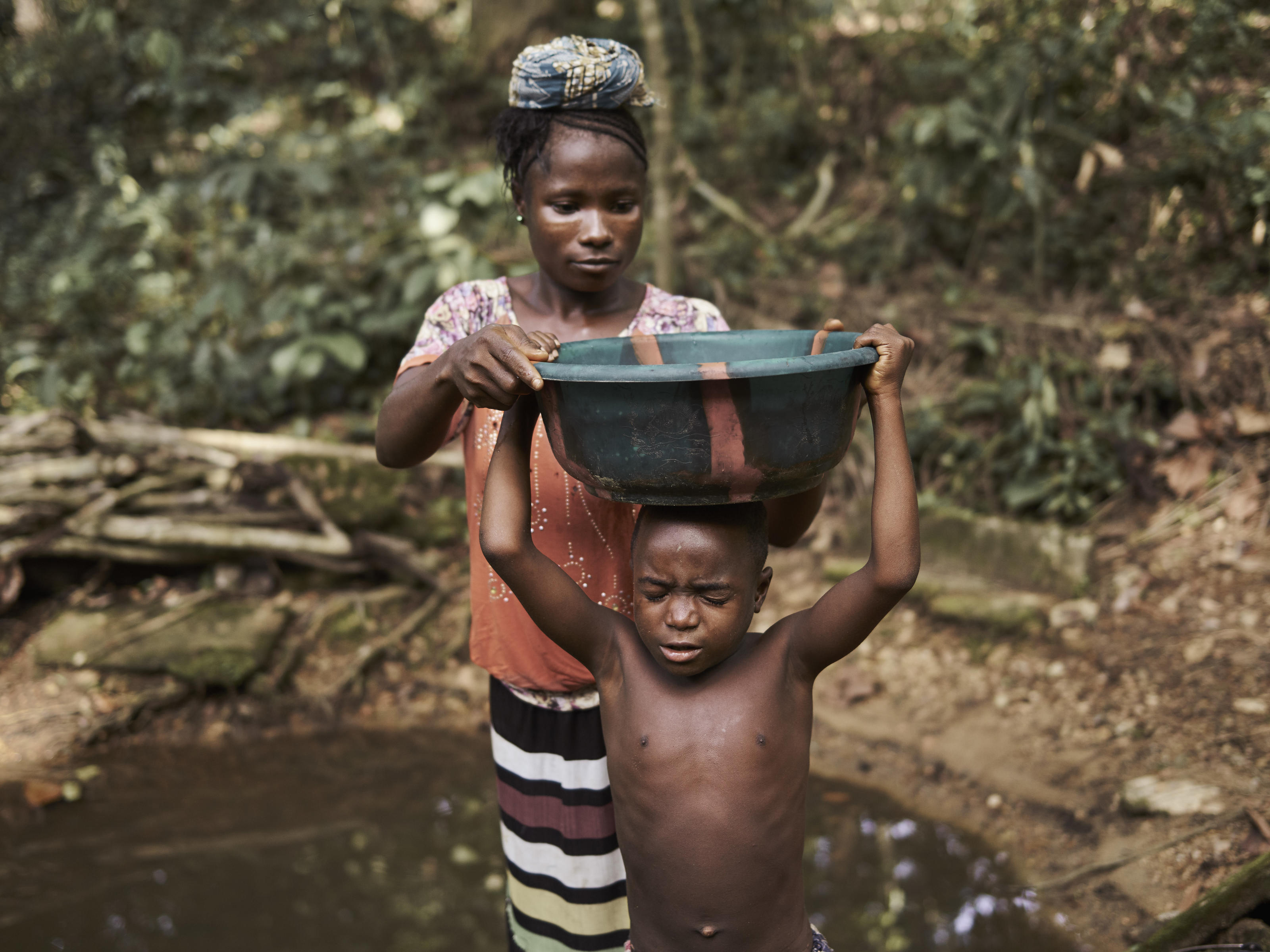 Matta Saffah, 27, puts a basin of dirty water on the head of her son Lahai, 7, after collecting it from a natural spring, the previous water source, in the village of Tombohuaun. Everyone in the village has experienced persistent problems with worms,  ...