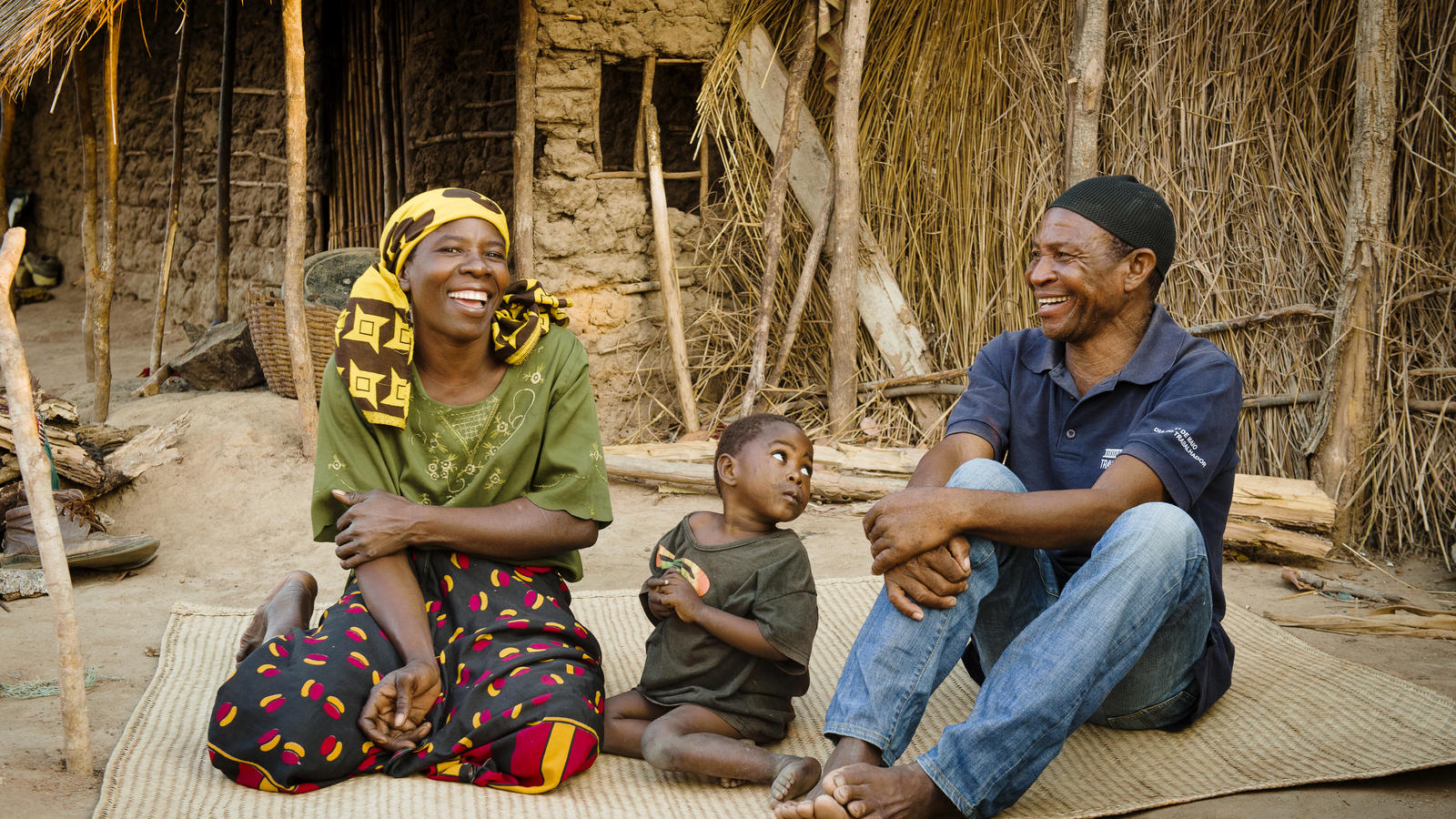 Said Amadi sits with his wife Helena Essiaca and their daughter Atija, 2, outside their home in Lacua village, Lunga District, Nampula Province, Mozambique, October 2017.