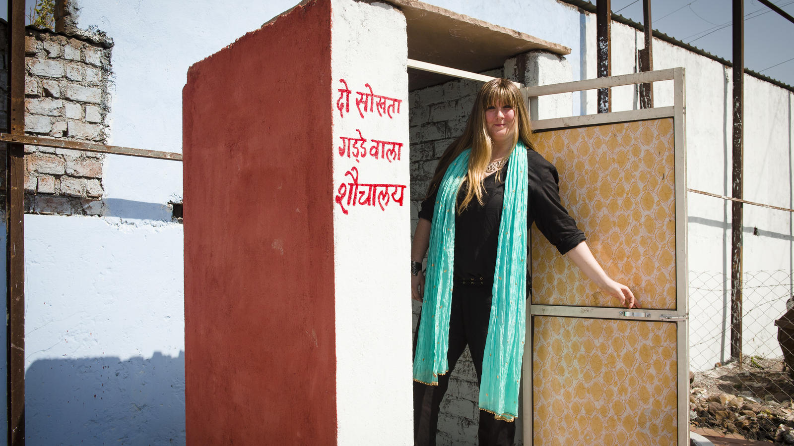 Glastonbury Festival Toilet Manager Jane Healy stands inside one of WaterAid India's toilets in Ujjain, India.