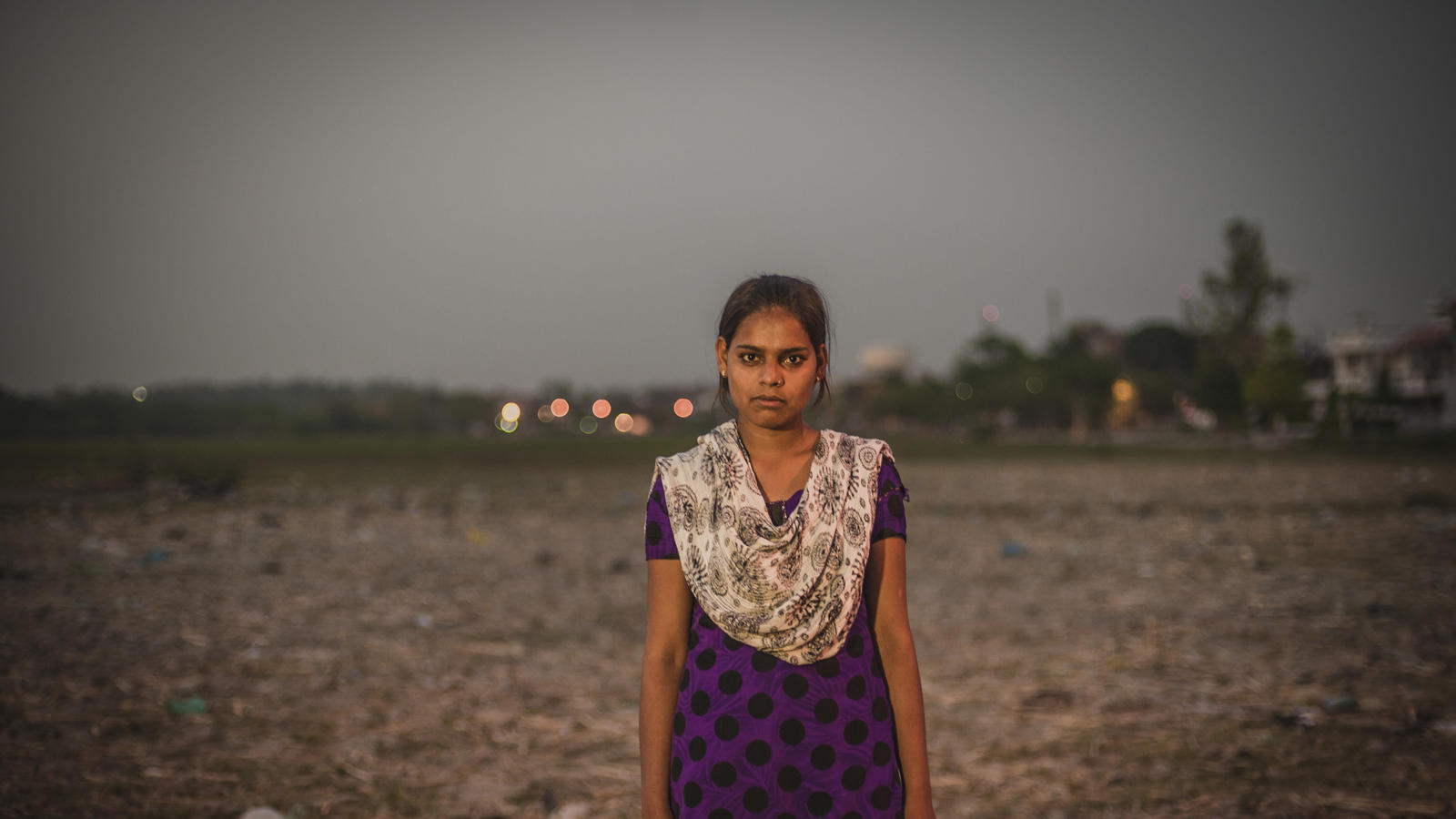 Kajal Gautam, 16, stands in front of a large open defacation area, Nihura Basti, Kanpur, India, 2014.