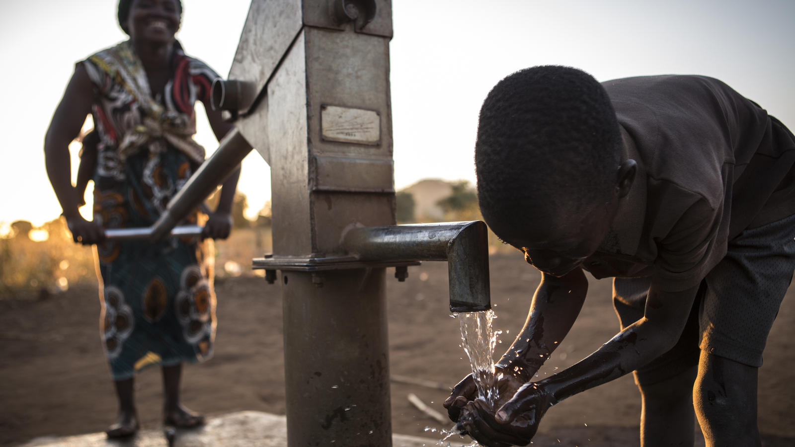 Karim drinks clean water from a hand pump in Malawi.