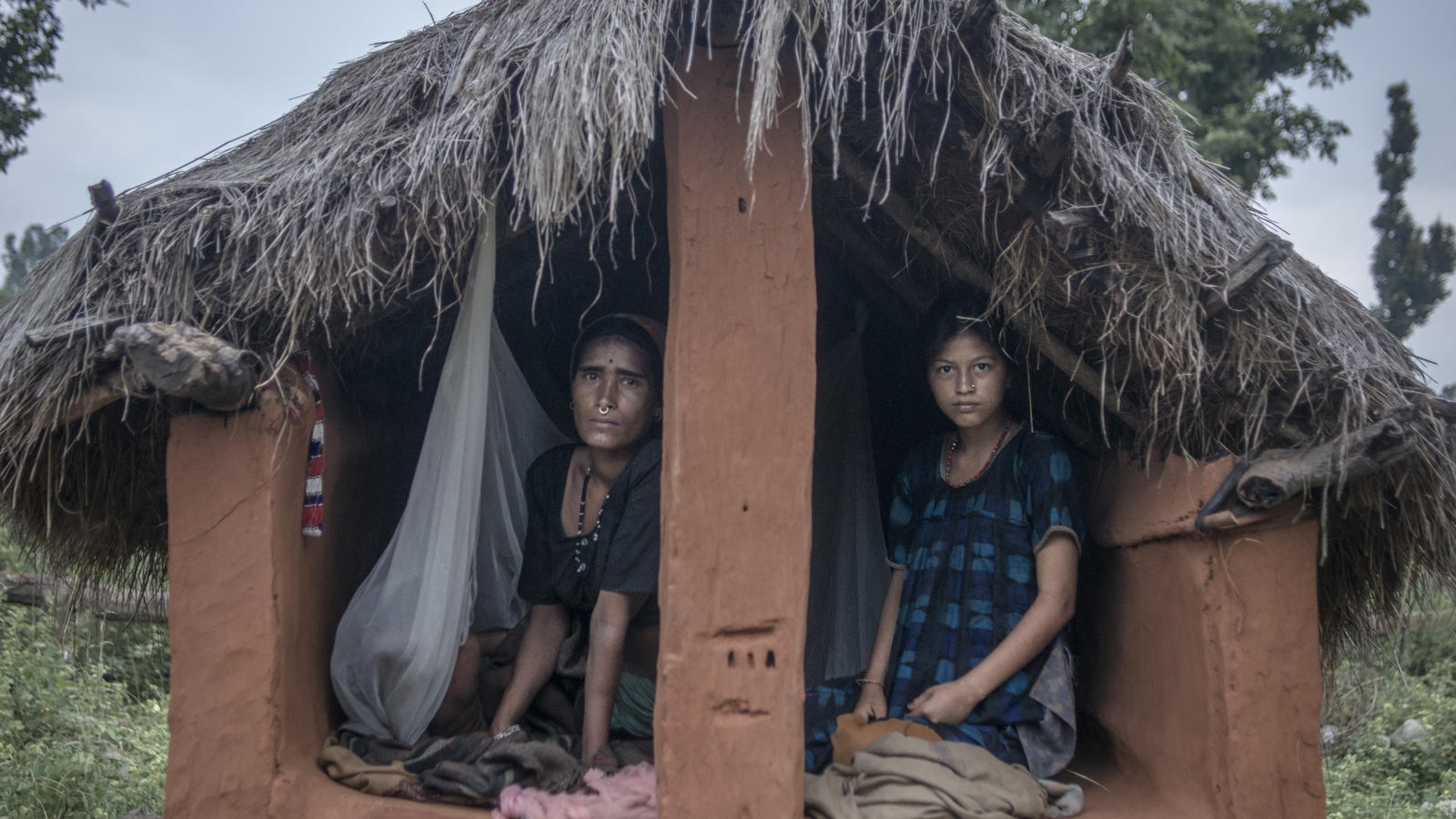 Mangu Bika, 14, shares the chaupadi hut with Chandra Tiruva, 34, to sleep in, Surkhet district, Nepal, 2013.