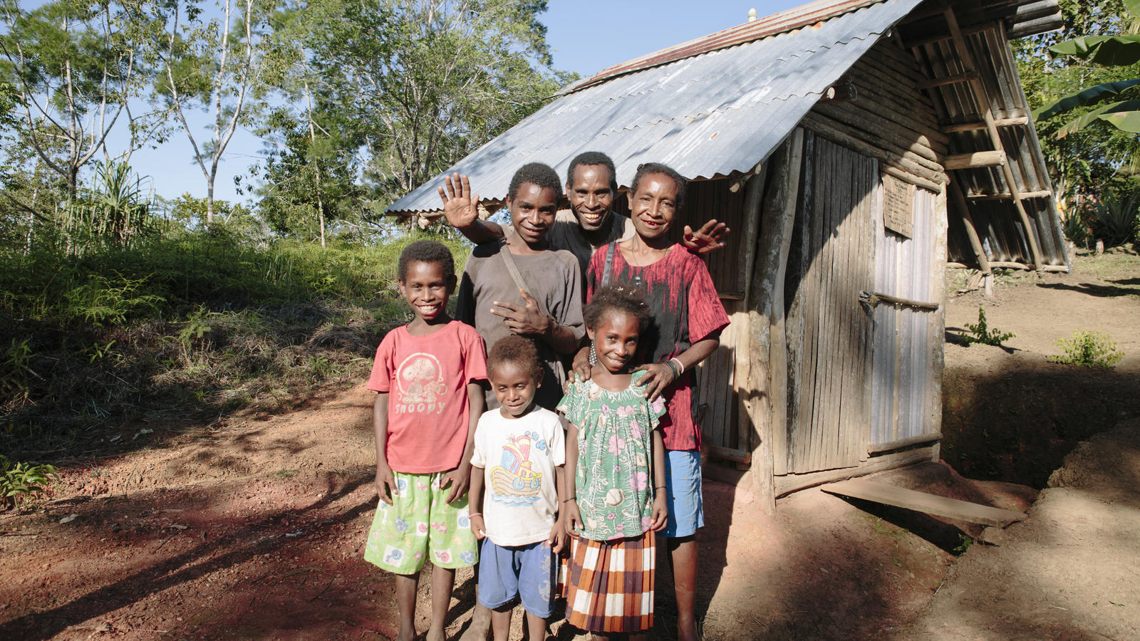 Andrew Kaiwa and his family stand in front of their new toilet in Mundangai village, Papua New Guinea.