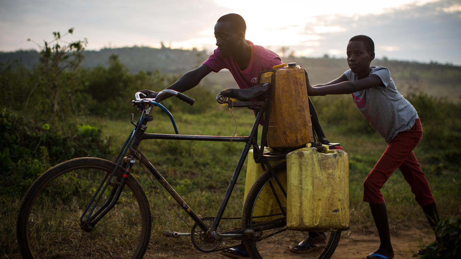 Jean-Bosco and Claire push their bike, now laden with jerrycans of water, back home, in Kibungo, Rwanda, February 2018.