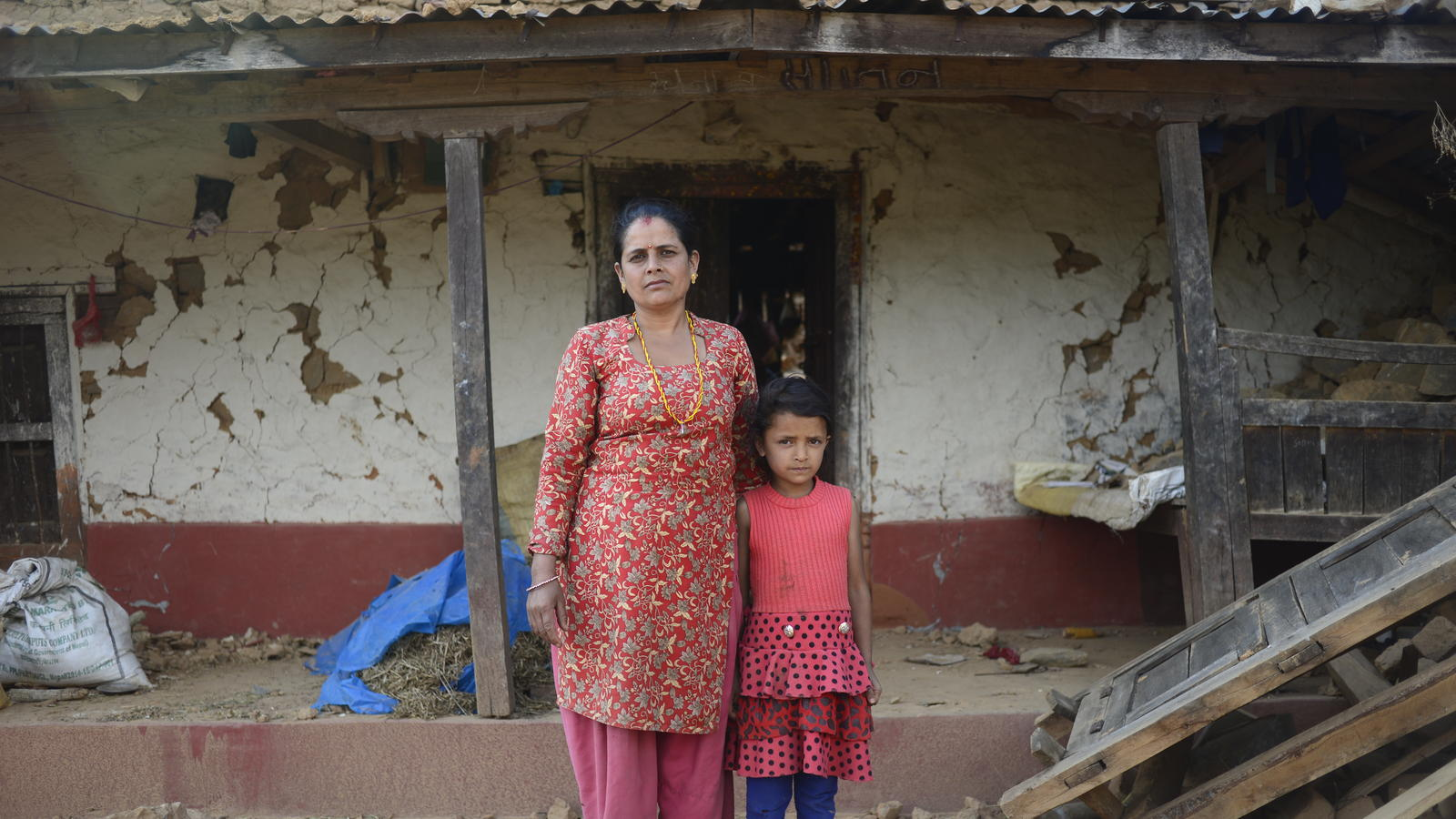 Maiya with daughter Sapana outside their badly-damaged house following earthquakes in Nepal