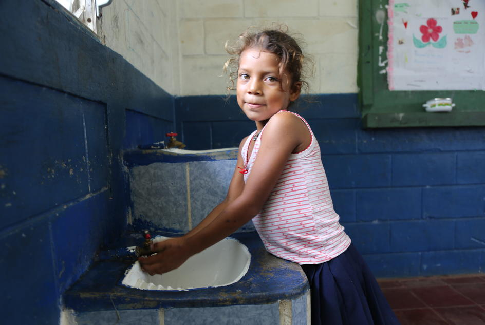 Young girl washes her hands at school.