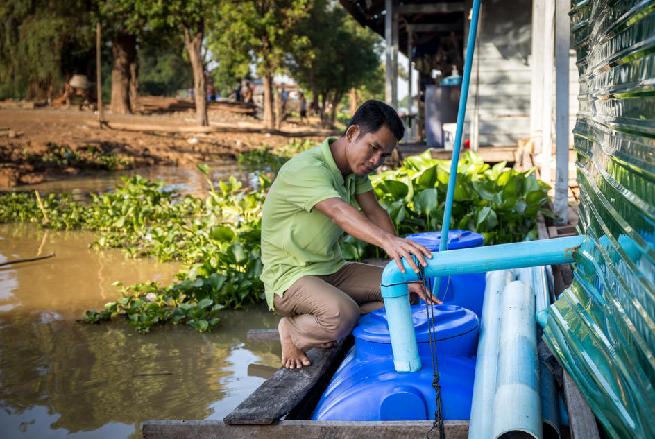 Hakley Ke, teacher, inspecting the HandyPod at a school in Tonle Sap, Cambodia.