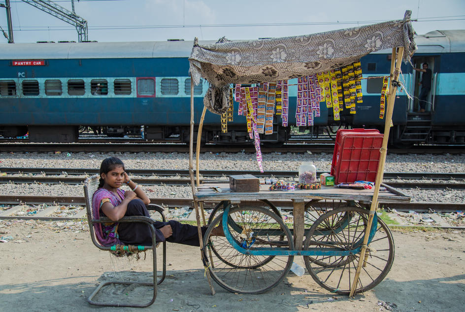 Nisha sits with her family's cart selling snacks by the railway side, Kanpur, India.