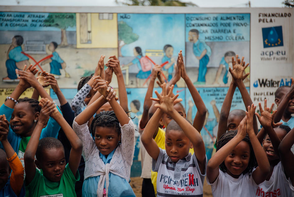Children perform a handwashing demonstration in front of the hygiene education mural at a primary school in Mavalane, Mozambique.