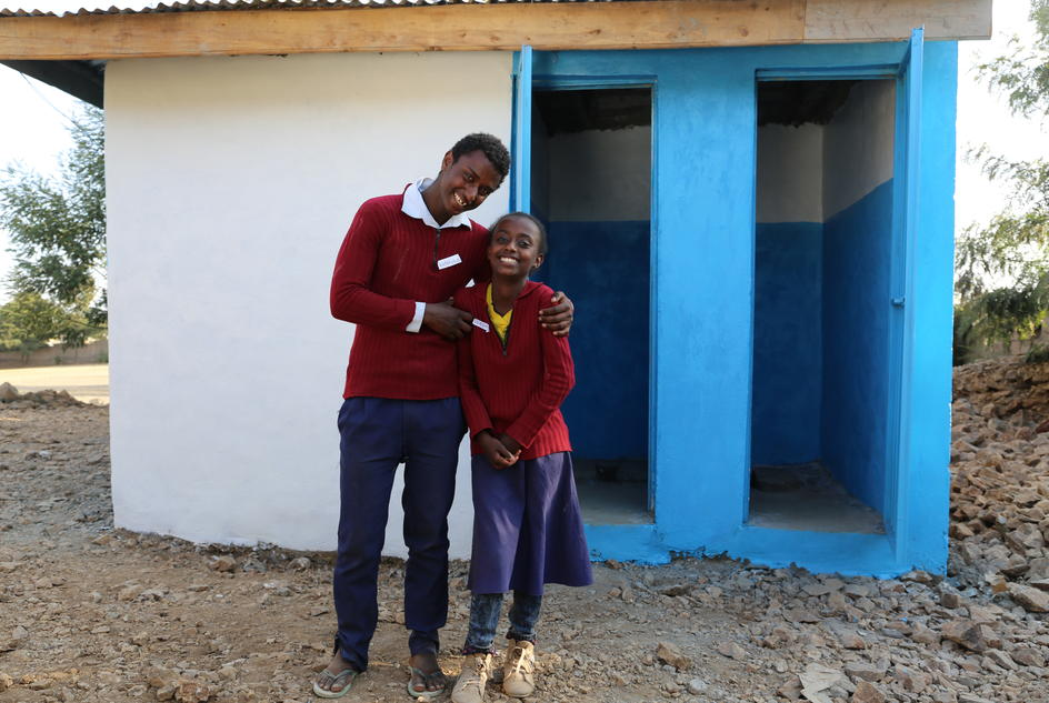 Melkamsira and Edilawit stand outside the toilets at their school in Ethiopia.