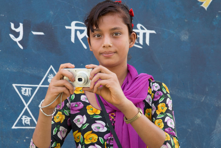 Manisha, a student in Sindhuli, Nepal, shows the camera she has used to take photographs of the taboos she encounters in daily life.