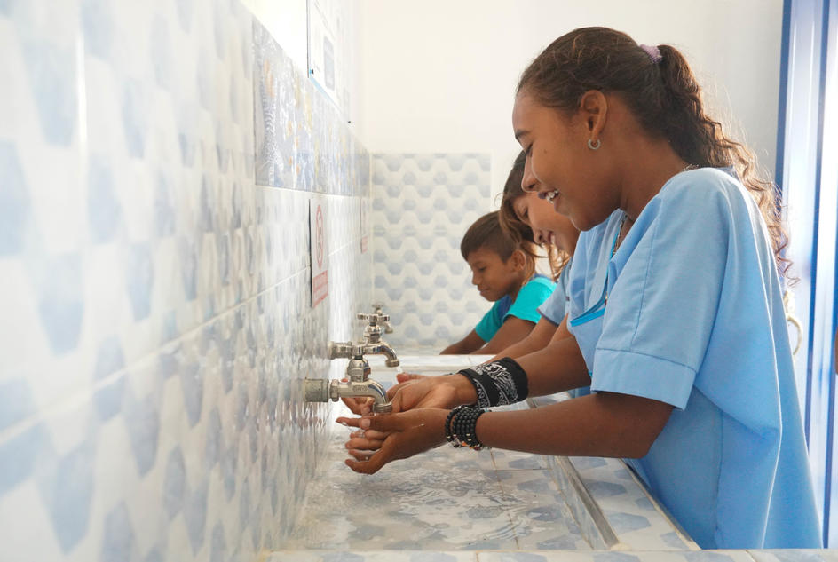 A student at Totcomana washes her hands at the new handwashing station.