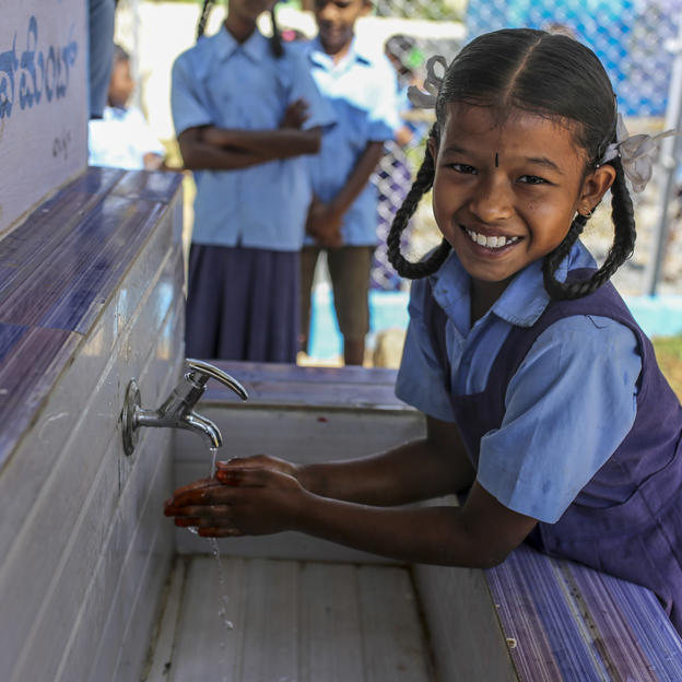With support from the PepsiCo Foundation, a girl uses the new handwashing station at a primary school in Karnataka, India.