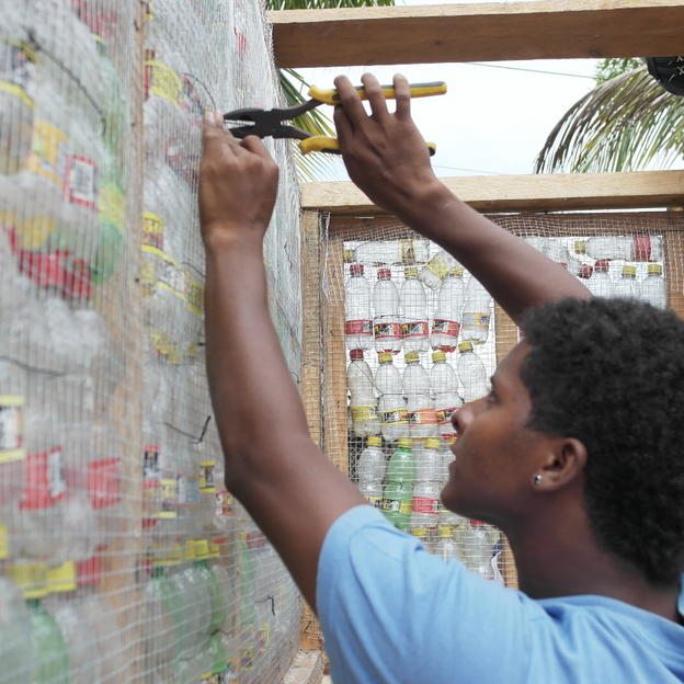 WaterAid trainee works on the construction of a sanitation module with recycled bottles