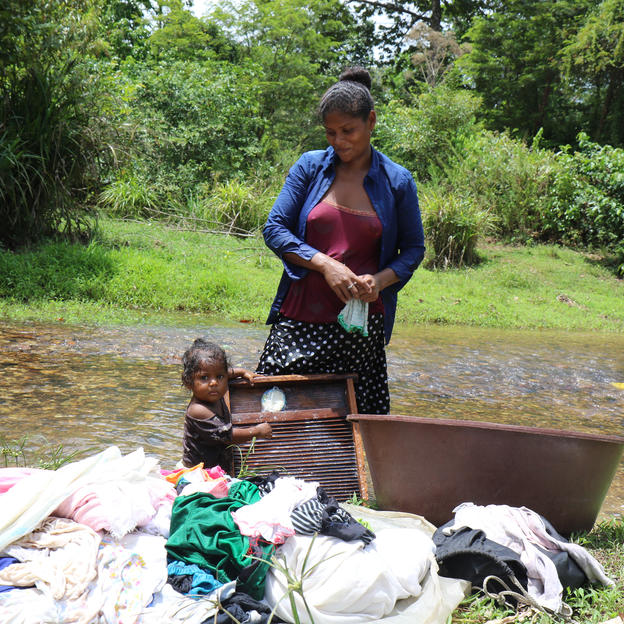 Woman with baby do laundry at the river in an indigenous community in Nicaragua.
