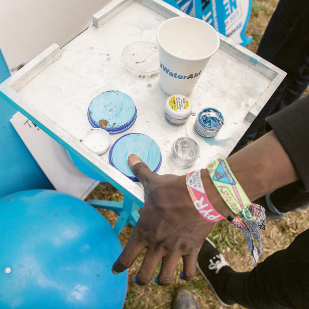 Malian band 'Songhoy Blues' visiting the WaterAid stand at the 2015 Glastonbury Festival. The band members gave out water to festivalgoers, signed the 'Make It Happen' petition, and left their thumbprints in blue paint on the campaign board.