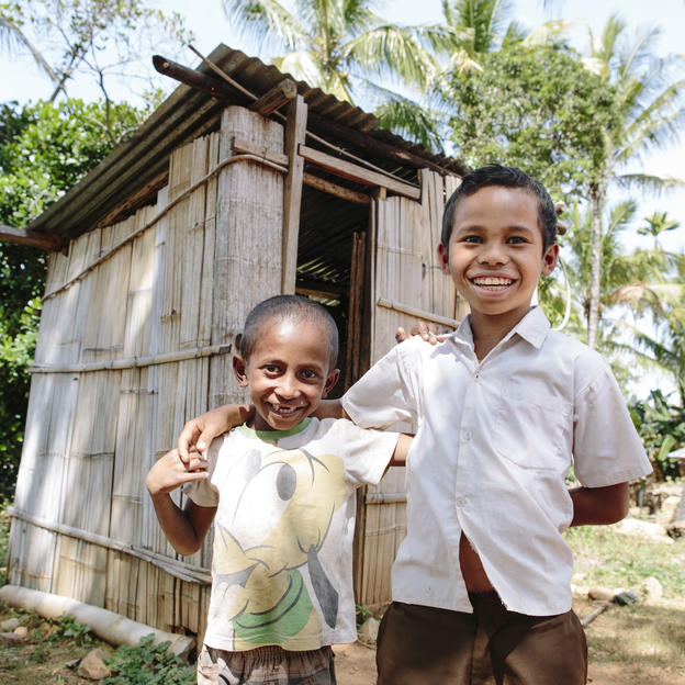 Narsizu and Fideris outside one of the new toilets in their village in Timor-Leste.