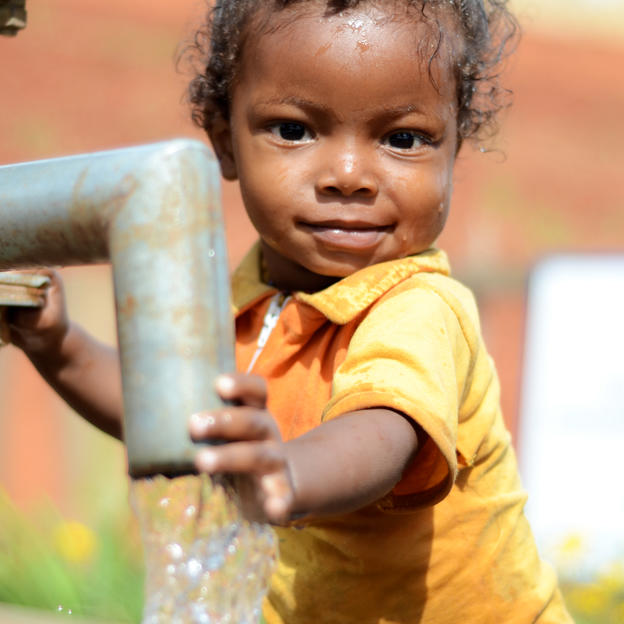 Portrait of Angelo playing with water at the water point in Ambohimatsinjo village, Antohobe commune, Vakinankaratra region, Madagascar. November 2015.