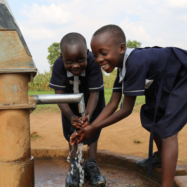 Two girls wash their hands at school in Uganda.