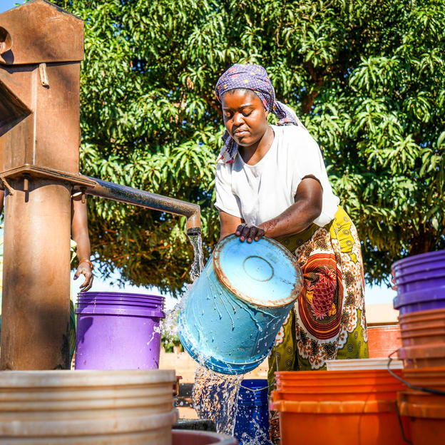 Ancha Da Gloria, 24, surrounded by a number of buckets while drawing water from the only borehole in Tropene Village, Memba District, Napula Province, Mozambique, May 2018.