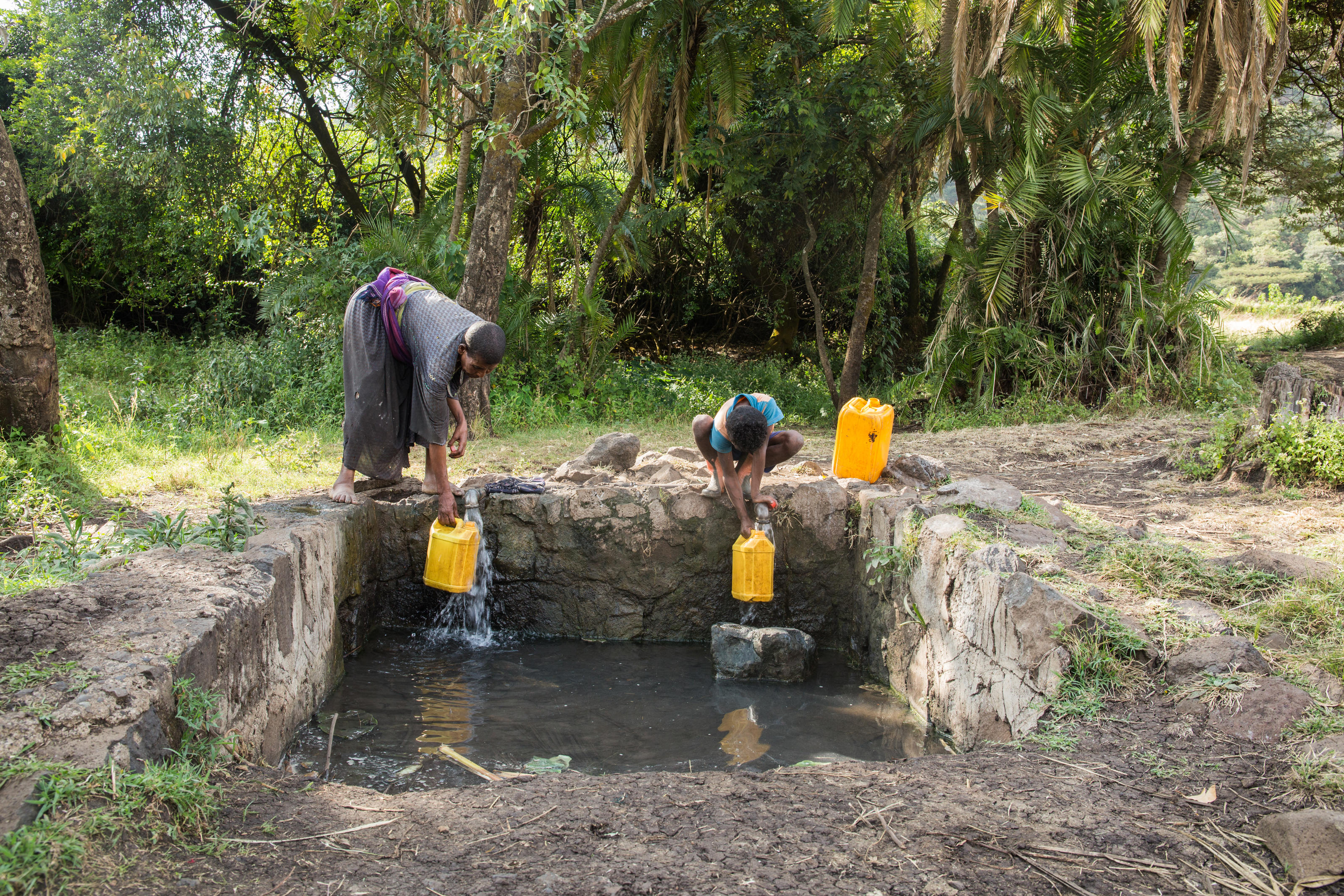 Tirunesh Alemu, employed by Yiraber Health Centre to fetch 40 litres of water per day, collecting water from the nearest water source 15-minutes walk away, Jabi Tehnan, West Gojjam, Ethiopia, December 2018.