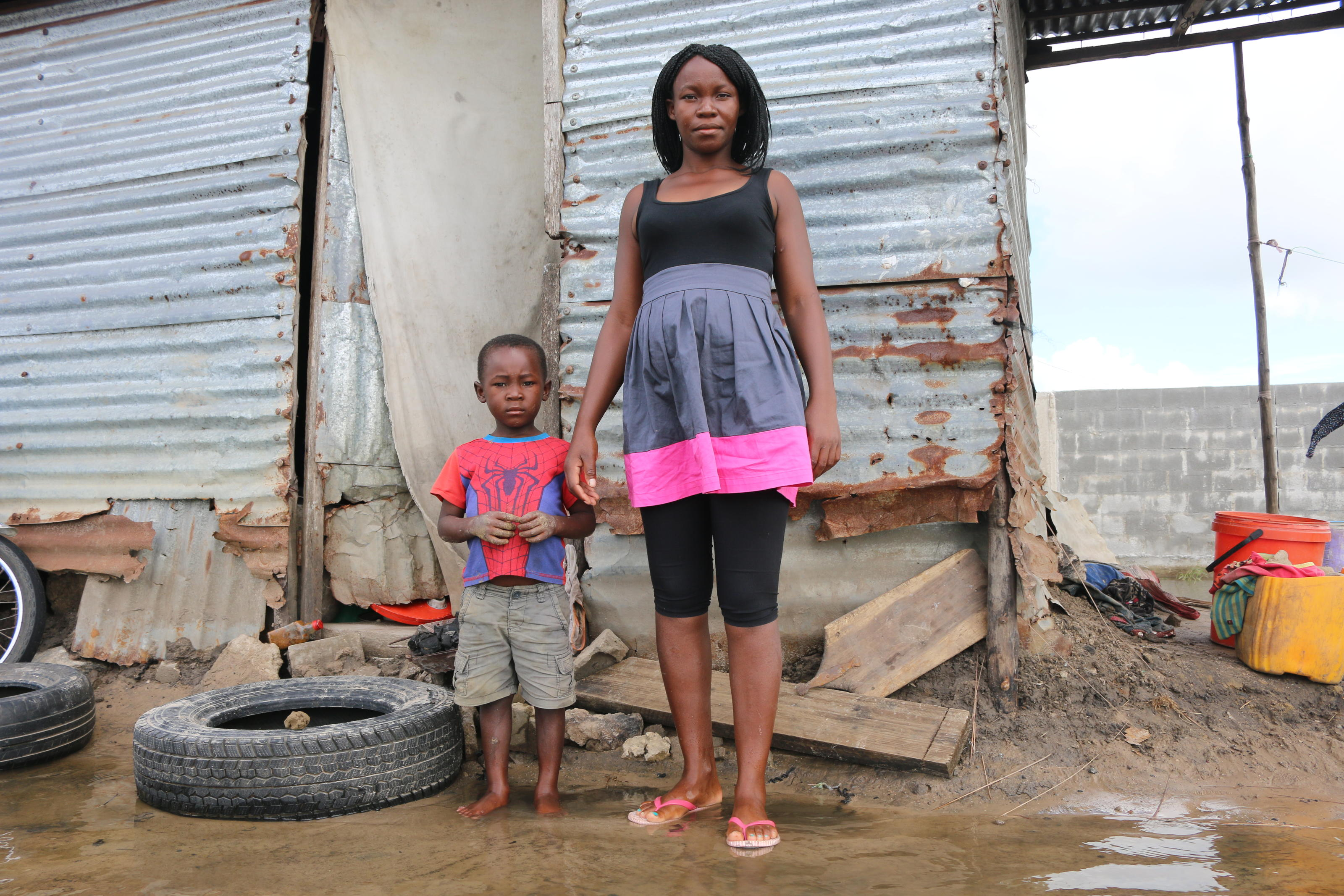 Zaida Eduardo, 24, stands in front of her mother's house. The house is surrounded by water and unfit to live in ,in Quelimane, Mozambique. March 2019.